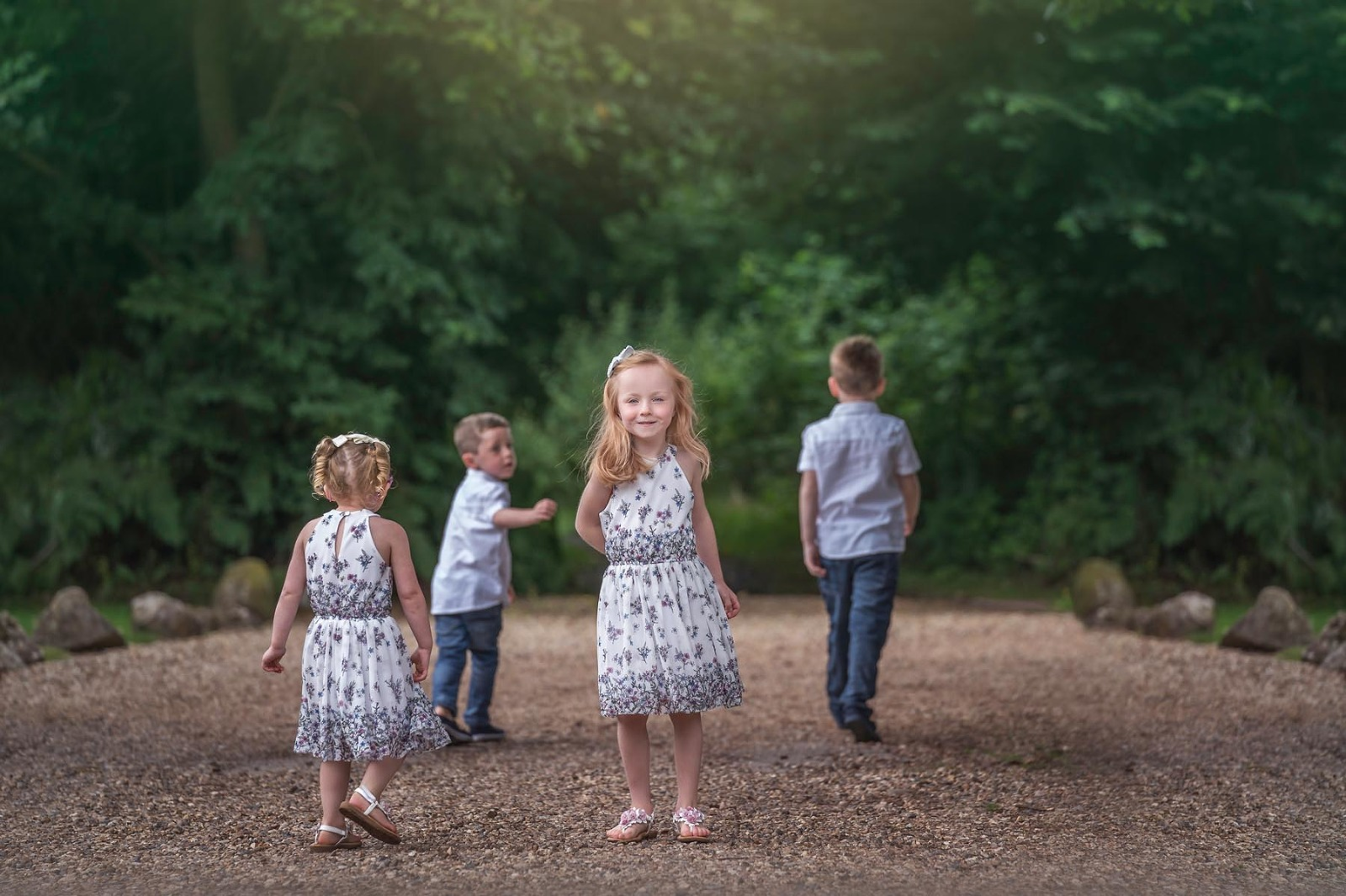 four children playing in the woods